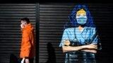 Një person në Prishtinë kalon pranë një murali dedikuar punëtorëve shëndetësorë, të cilët janë në vijën e parë të frontit në përballje me pandeminë.
