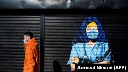 Një person kalon pranë një murali në Prishtinë dedikuar punëtorëve shëndetësorë, për luftën e tyre kundër pandemisë.