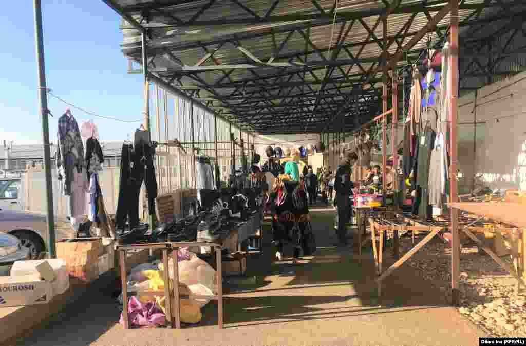 Қарабұлақ ауылындағы мал базарына кіреберісте киім-кешек сатып тұрған адамдар.