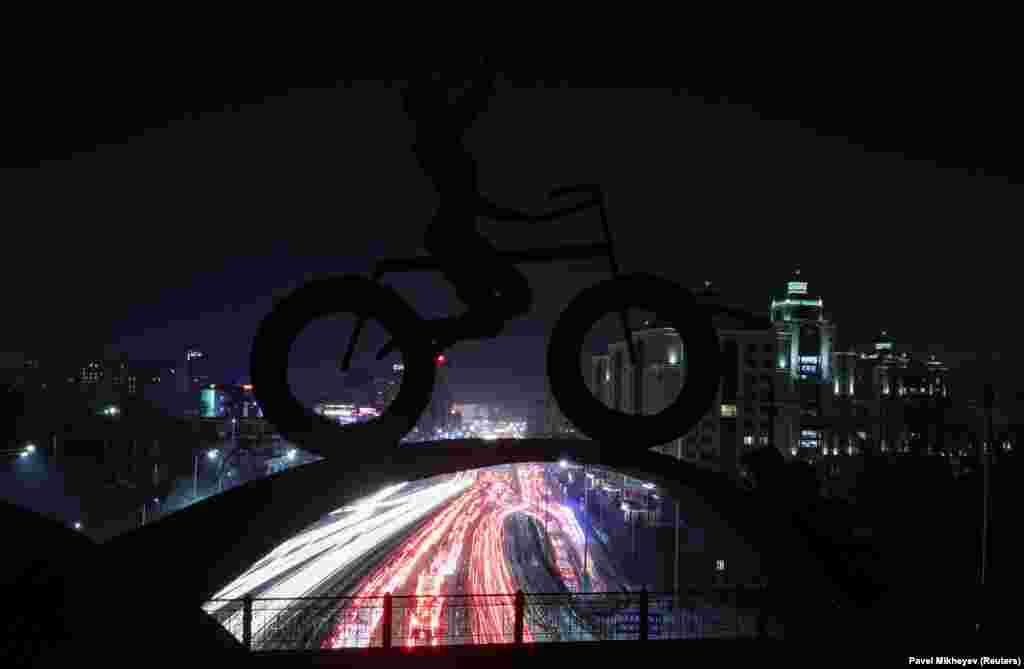 Traffic flows along Al-Farabi Avenue with a sculpture of a bicyclist in the foreground in Almaty, Kazakhsta. (Reuters/Pavel Mikheyev)