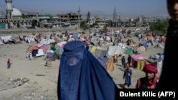 A burqa-clad woman stands by a displacement camp in Kabul on September 17.