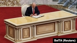 "Alyaksandr Lukashenka signs a document after taking the oath of office during a hastily called ""inauguration"" in Minsk on September 23."