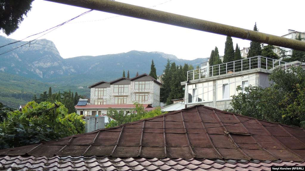 Кримські гори видніються вдалині над дахами – це традиційний краєвид із вікна в Гурзуфі