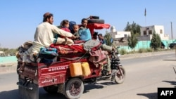 Residents flee Nadali district to Helmand's provincial capital, Lashkar Gah, during the ongoing clashes between Taliban fighters and Afghan security forces on October 14.