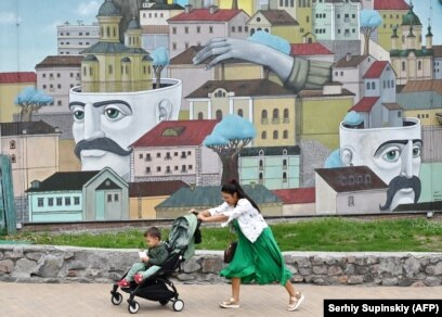 A woman pushes a stroller with her son in front of a mural in Kyiv.