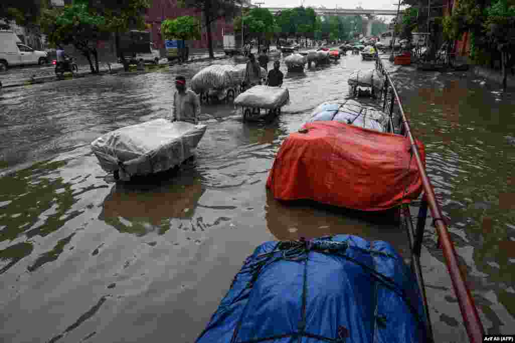 Street vendors pull their carts as they wade through a flooded street after heavy monsoon rains in Lahore, Pakistan. (AFP/Arif Ali)