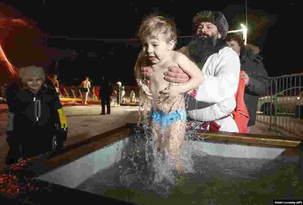 Чоловік занурює хлопчика в холодну воду в Санкт-Петербурзі, Росія