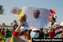 Një grua mban një fotografi të Papa Françeskut, në afërsi të Aeroportit të Bagdadit, ndërsa pret që ai të arrijë.