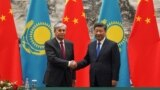 Chinese President Xi Jinping (right) shakes hands with Kazakh President Qasym-Zhomart Toqaev at the end of a signing ceremony at the Great Hall of the People in Beijing on September 11, 2019.