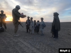 Soldați români dau cadouri copiilor afgani