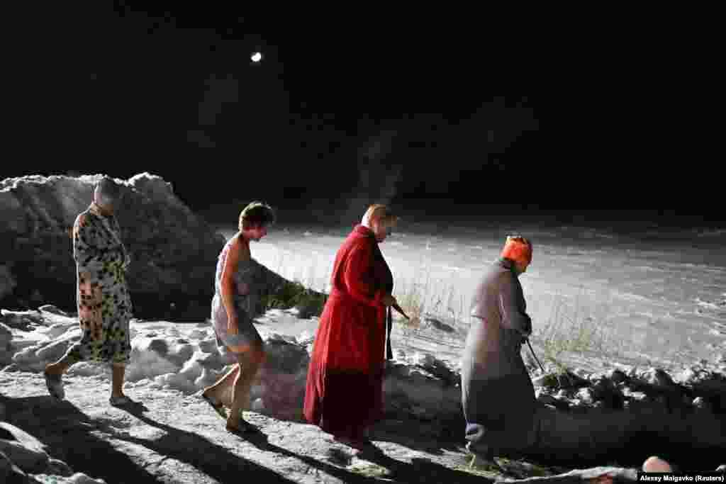 Women walk to take a night swim in the village of Kormilovka in Russia's Omsk region.
