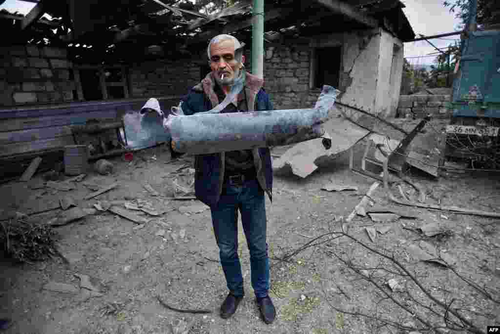 A man shows a shell fragment in the yard of his brother's house, which was damaged by shelling during fighting between Armenia and Azerbaijan over the breakaway Nagorno-Karabakh region, in the disputed region's city of Martuni on October 1. (AFP)