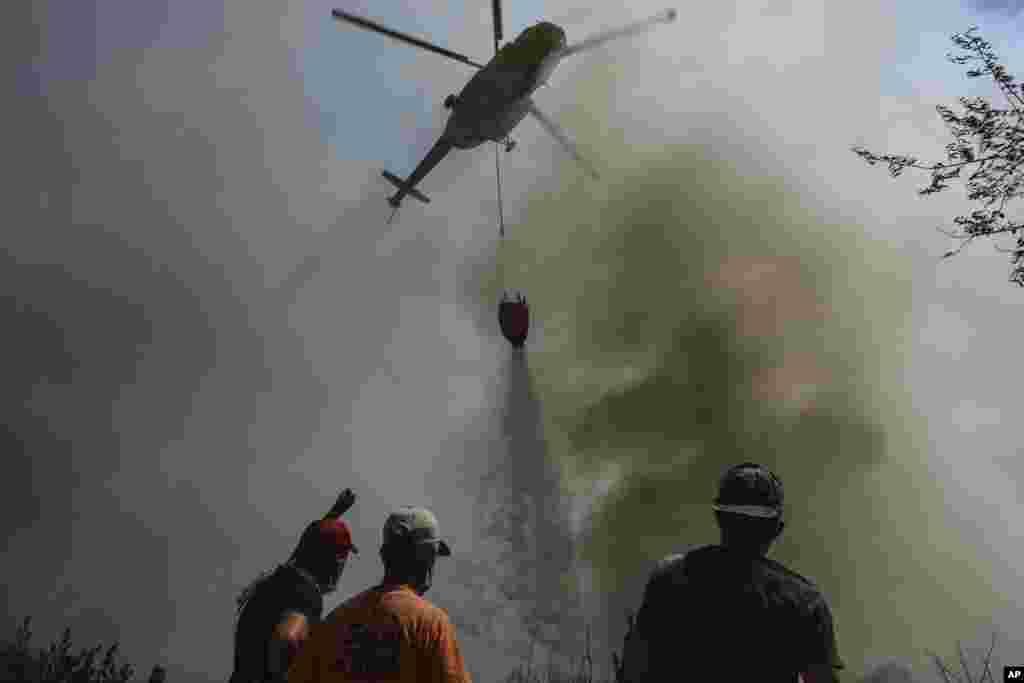 Një helikopter duke hedhur ujë mbi fshatin Sirtkoi, të shkrumbuar nga zjarri, afër Manavgatit, në Antalia. (1 gusht)