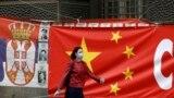 Një grua në Beograd kalon pranë një flamuri të Kinës. Foto nga arkivi.