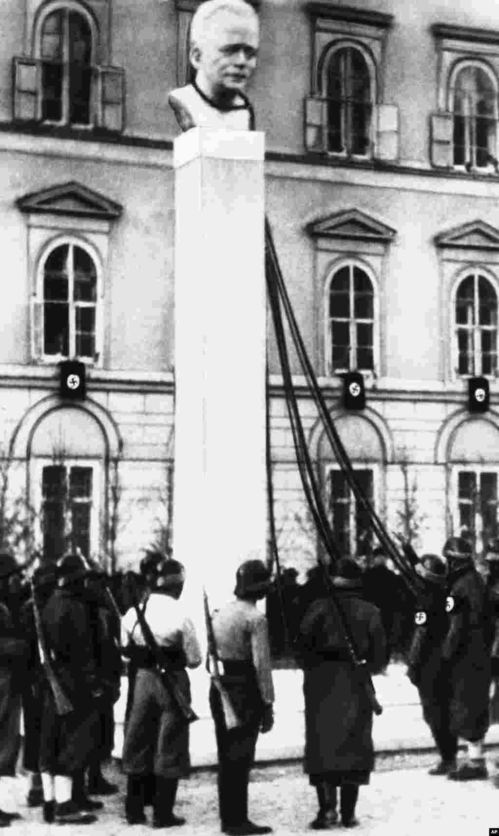 Нацистки войници в очакване на заповед за сваляне на бюста на австрийския канцлер Енгелберт Долфус. Това се случва след анексията на Австрия от нацистка Германия през 1938 г.