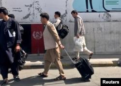 Afghan passengers walk toward the airport in Kabul on August 15.