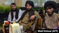Talibani așteptând să fie serviți într-un restaurant în Kabul, joi 26 august, 2021.