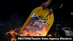 A nukleáris egyezményből kilépő Donald Trump fotóját égetik egy teheráni tüntetésen 2018-ban.