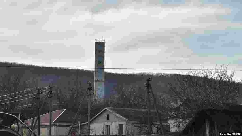 2021 рік, Севастополь. На водонапірній вежі збереглося зображення жовто-синього прапора, над ним – майже непомітний силует українського герба