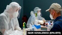Медики в защитных костюмах принимают пациентов в одном из временных стационаров в Бишкеке. Июль 2020 года.