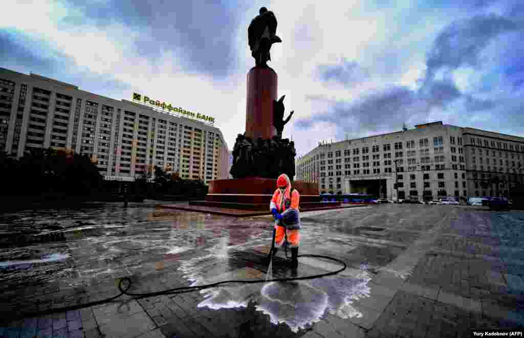 A municipal worker wearing a face mask and a protective suit to protect against the coronavirus disinfects a square near the Lenin monument in central Moscow. (AFP/Yuri Kadobnov)