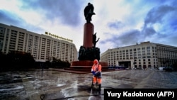 A municipal worker wearing a face mask and a protective suit to protect against the coronavirus disease disinfects a square near Lenin's monument in central Moscow on October 19.