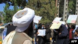 A member of the Taliban watches as Afghan women hold placards during a protest in Herat earlier in September.