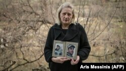 Lusine Margarian holds photographs of her son Hayk, 23, an Armenian soldier who went missing during last year's war with Azerbaijan, in Yerevan on March 7.