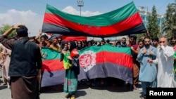 Люди несут национальный флаг во время акции протеста, прошедшей в День независимости Афганистана в Кабуле, Афганистан, 19 августа 2021 года
