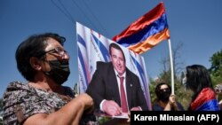 ARMENIA -- A supporter of Armenian opposition leader Gagik Tsarukian holds its portrait during a unauthorized rally close to National Secuirury Service headquarter in Yerevan, June 14, 2020