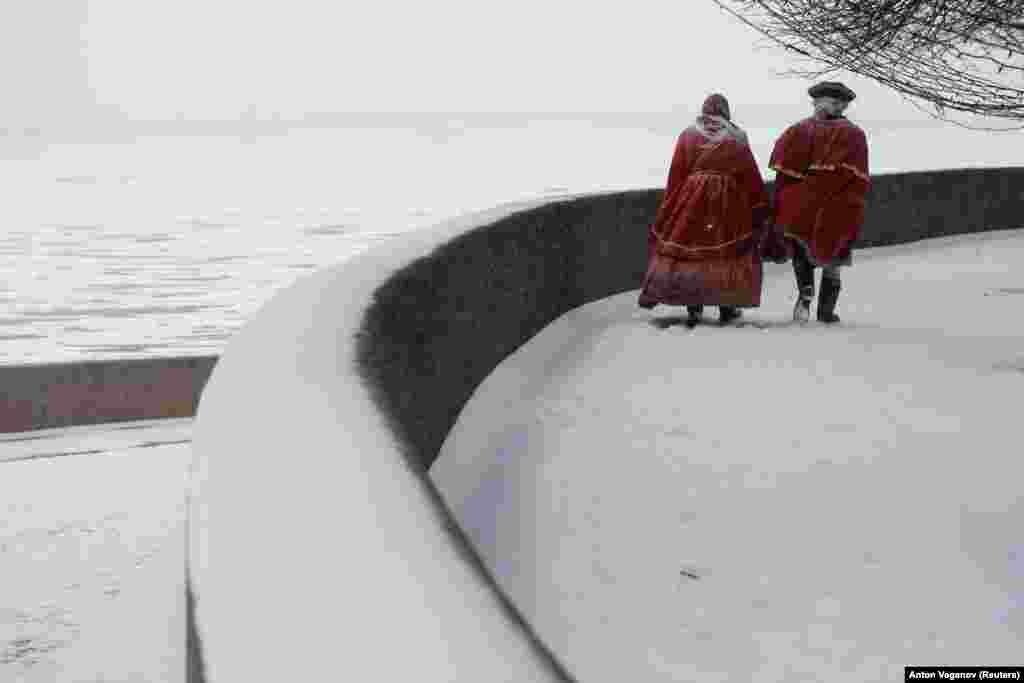 Ulični zabavljači odjeveni u staru nošnju šetaju uz obalu ostrva Vasilievski za vrijeme sniježnih padavina u centru Sankt Peterburga. (Reuters / Anton Vaganov)