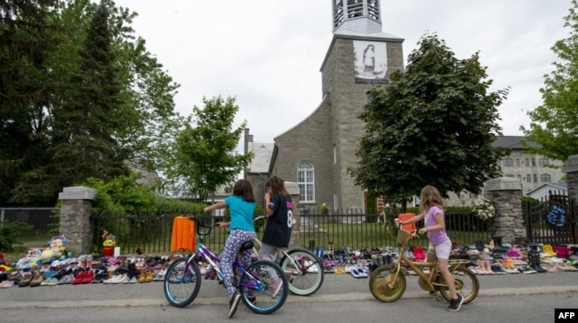Disa fëmijë të një lagjeje në Kubek, ndalen për të shikuar qindra palë këpucë të lëna afër një kishe, për të kujtuar 215 fëmijët indigjenë, eshtrat e të cilëve janë gjetur në një shkollë rezidenciale në maj të vitit 2021.