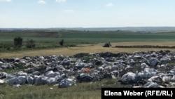 Трактор делает земляное ограждение территории мусорного полигона