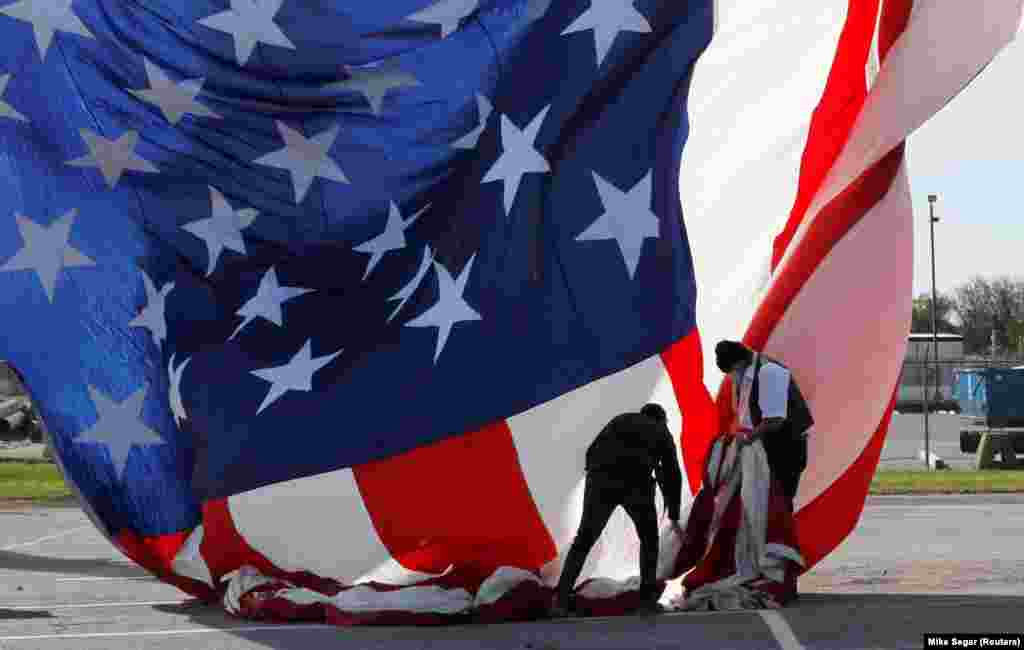 Workers hang a giant American flag at the location of the election night rally for Democratic U.S. presidential nominee and former Vice President Joe Biden on Election Day, in Wilmington, Delaware, U.S., November 3, 2020.