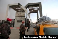 A palesztin biztonsági erők tagjai őrködnek, miközben egy utasokat szállító taxi érkezik az Egyiptommal közös rafahi határátkelő kapujához a Gázai övezet déli részén, 2021. február 23-án