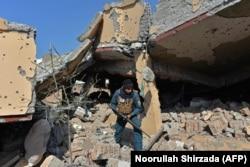 Сотрудник афганских служб безопасности осматривает жилой дом, который был разрушен в ходе вооруденного столкновения между правительственными силами и боевиками группы ИГ в Джелалабаде в феврале 2021 года