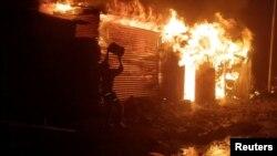 Человек пытается потушить пожар в здании после извержения вулкана на горе Ньирагонго, поздно вечером 22 мая 2021 года в окрестностях Гомы, Демократическая Республика Конго. Фото: Reuters
