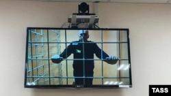 Ресейдің Владимир облысындағы қамау мекемесінде жазасын өтеп жатқан Алексей Навальный (экранда) өз шағымы қаралған сотқа онлайн қатысып тұр. 7 маусым 2021 жыл.