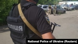 Ukrainian law enforcement officers are seen near a site where a man armed with a grenade is holding a police officer hostage in Poltava on June 23.
