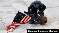 Un polițist arestează o demonstrantă pro-Trump în timpul violențelor declanșate de suporterii președintelui perdant la clădirea Capitoliului, Washington, 6 ianuarie 2021