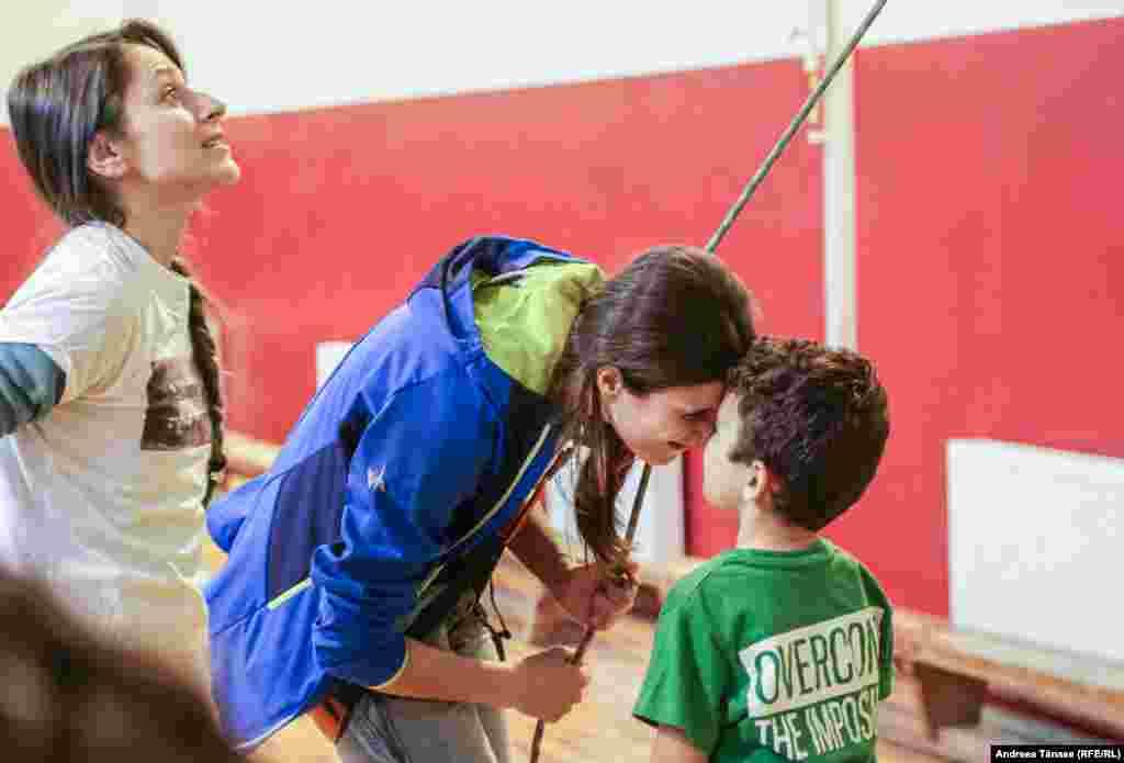 """Ana Anton, instructor și PR la Climb Again, salută un copil cu deficiență de auz de la Școala Profesională Specială pentru Deficienți de Auz """"Sfânta Maria"""" din București."""