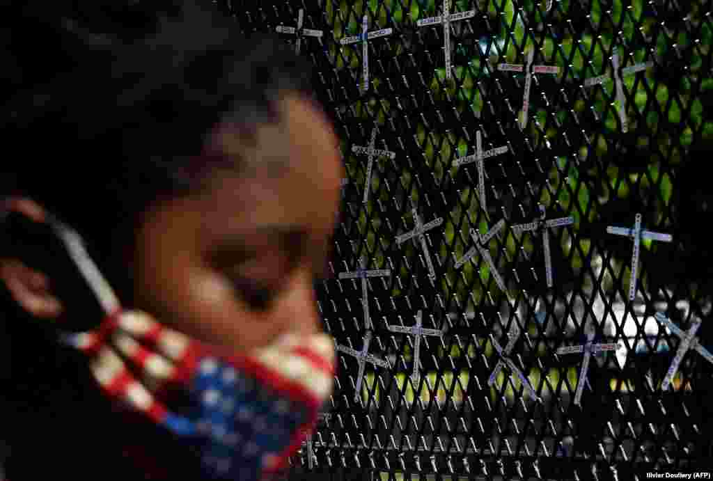 A demonstrator pauses in front of a wall displaying names of black people who have been killed by police, across from the White House during a peaceful protest against police brutality and the death of George Floyd, on June 7, 2020 in Washington, DC.