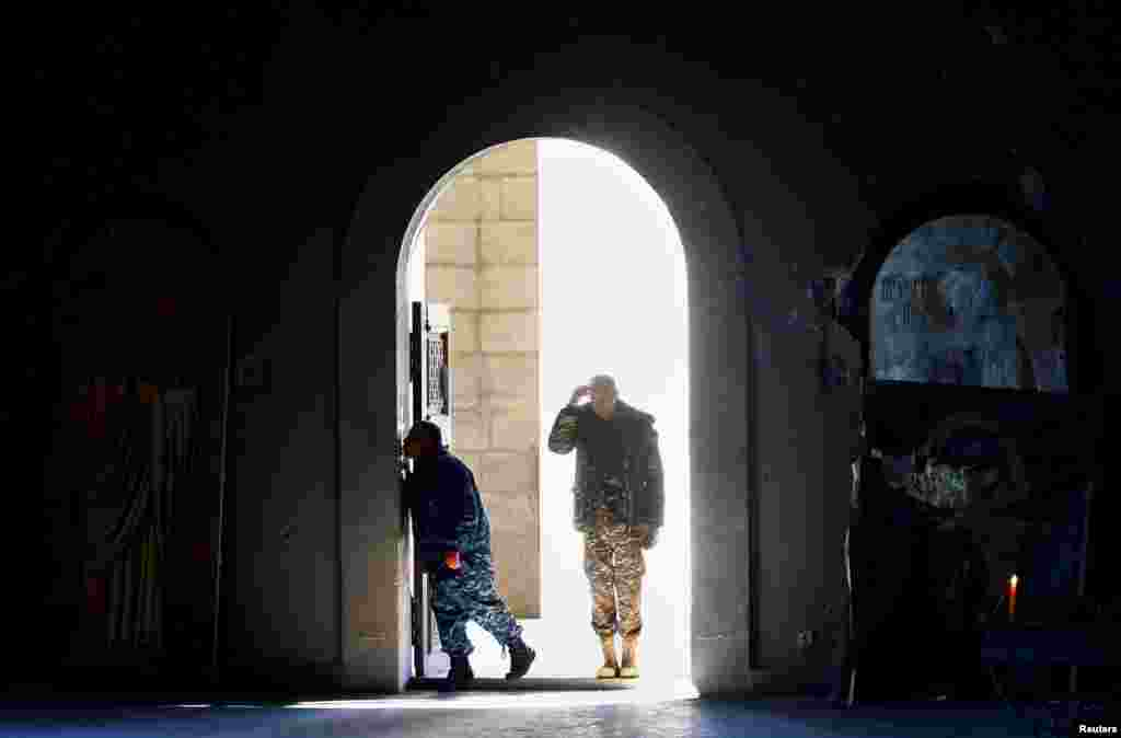 Men in Shushi (Susa) enter a cathedral damaged by shelling during the military conflict over Nagorno-Karabakh. (Reuters/Stringer)