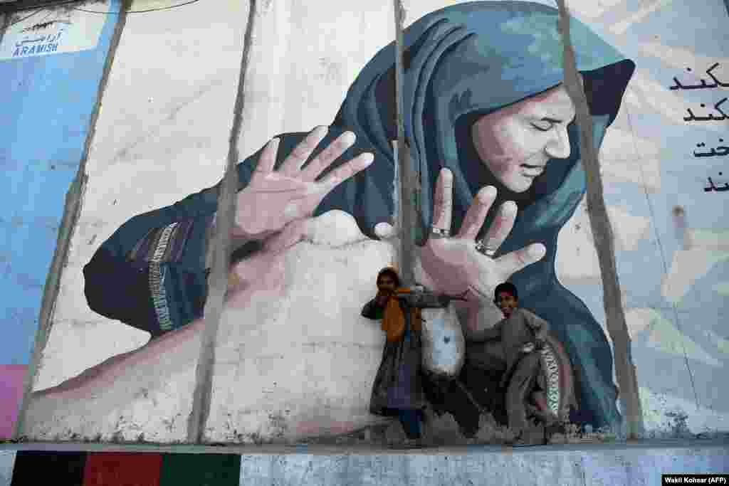Afghan children carrying a sack with garbage walk past a mural along a roadside in Kabul. (AFP/Wakil Kohsar)
