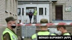 Rendőr beszélget egy karantén miatt bezárt szálló lakójával a Kijev melletti Visnynevében, 2020. április 24-én