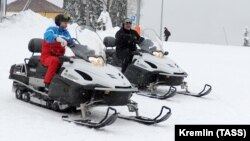 Russian President Vladimir Putin (left) and his Belarusian counterpart Alyaksandr Lukashenka ride snowmobiles following their talks in Sochi on February 22.