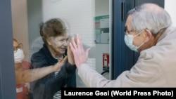 По време на пандемията във Франция 75-годишният Ив идва на посещение на жена си Жозиан (82 г.), която е в старчески дом. Снимката на Лоранс Же печели трето място в World Press Photo Contest 2021.