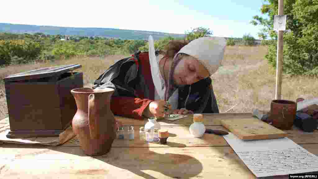 Средневековый писарь показывает мастерство каллиграфии в лагере на Федюхиных высотах