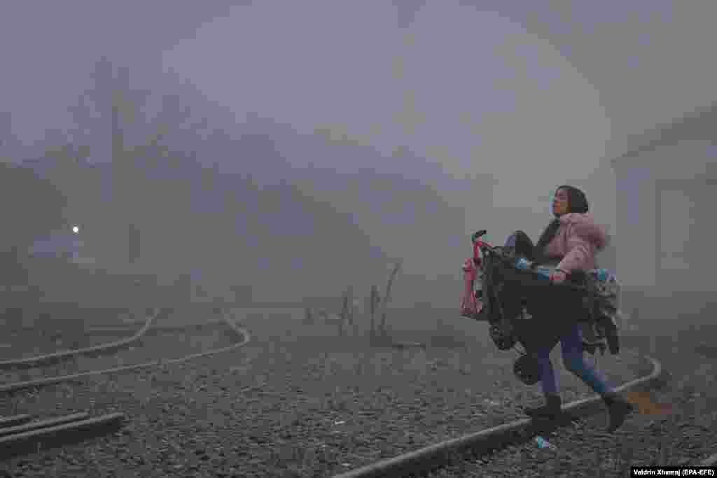 A woman carries her child through early morning fog and pollution in the Fushe Kosove district of the Kosovar capital,Pristina. (epa-EFE/Valdrin Xhema)