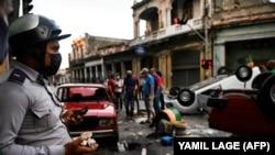Tüntetők egy csoportja rendőrautókat borított fel Havannában 2021. július 11-én